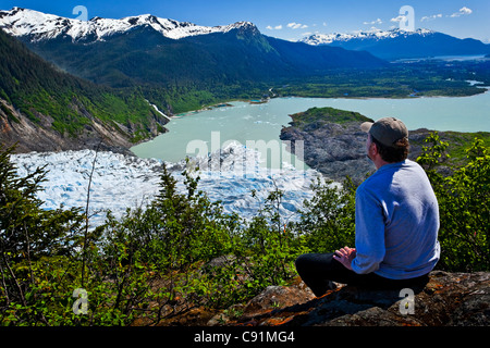 A male hiker looking down onto Mendenhall Glacier and Mendenhall Lake from West Glacier Trail, Juneau, Southeast - Stock Photo