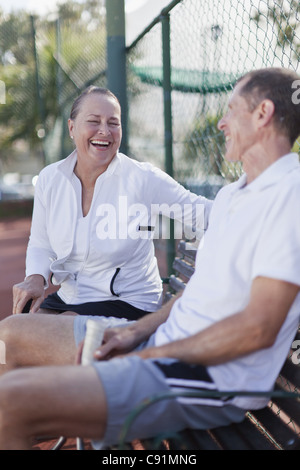 Older couple talking on park bench - Stock Photo