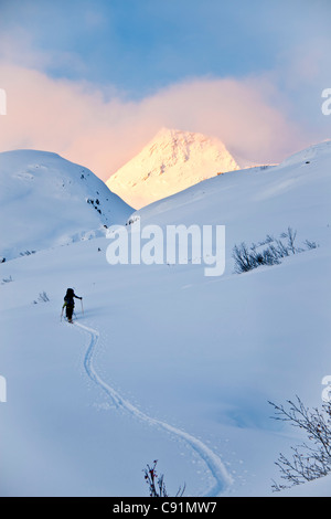 Skiers skiing uphill above Thompson Pass on Girls Mountain near Valdez, Winter in Southcentral Alaska - Stock Photo