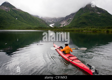 Woman sea kayaking in Silver Horn area of Lake Beverly in Wood Tikchik State Park, near Dillingham, Summer in Southwest - Stock Photo
