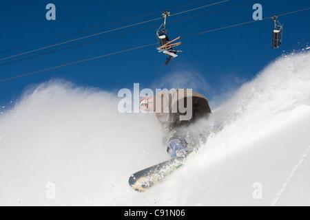 Snowboarder in fresh powder at Alyeska Resort with ski lift overhead, Girdwood, Southcentral Alaska, Winter - Stock Photo
