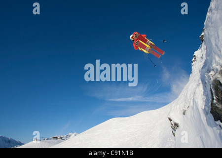 Downhill skier makes an extreme jump from a ledge while skiing at Alyeska Resort, Southcentral Alaska, Winter - Stock Photo