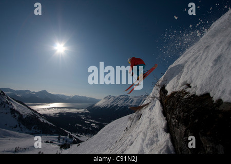 Silhouette of a downhill skier makes an extreme jump from a ledge while skiing at Alyeska Resort, Southcentral Alaska, - Stock Photo