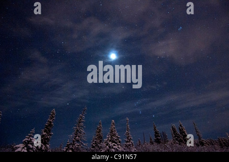 Full moon and a starry winter night over the hillside area above Anchorage, Southcentral Alaska, Winter - Stock Photo