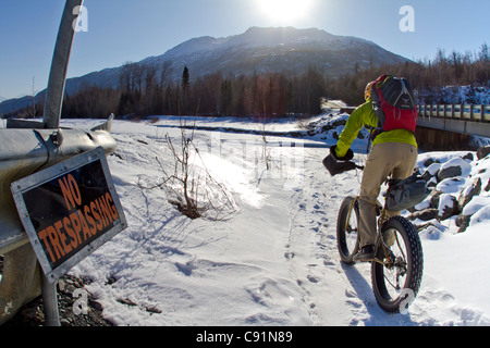 Man biking past a No Trespassing sign along the Knik River to the Knik Glacier on a fat tire bicycle, Chugach Mountains, - Stock Photo