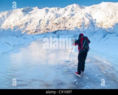Man Nordic ice skating on the frozen Placer River, Kenai Mountains, Southcentral Alaska, Winter - Stock Photo