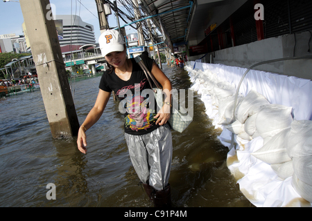 A woman wading through floodwaters on street  on November 8, 2011 in ladprao district, Bangkok , Thailand. Over - Stock Photo