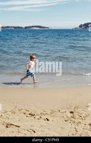 Boy running in waves on beach - Stock Photo