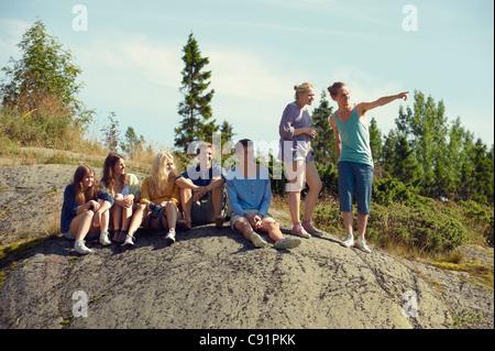 Friends sitting together on boulder - Stock Photo