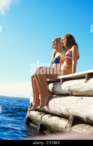 Teenage girls dangling legs over pier - Stock Photo