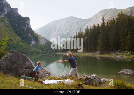 Father and son pitching a tent by lake - Stock Photo