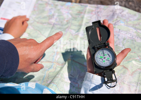 Father and son using compass and map - Stock Photo