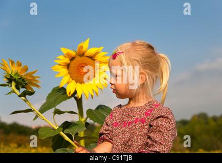 Girl holding sunflower outdoors - Stock Photo