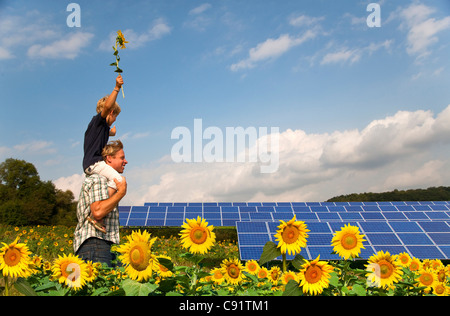 Father and son in field by solar panels - Stock Photo