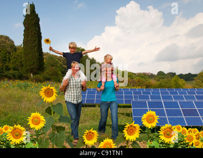 Family in field by solar panels - Stock Photo