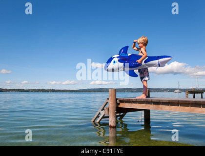 Boy holding inflatable whale on dock - Stock Photo