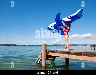 Girl holding inflatable whale on dock - Stock Photo
