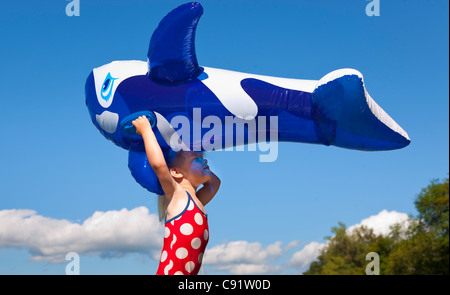 Girl holding inflatable whale outdoors - Stock Photo