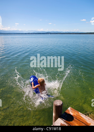 Boy floating in lake with toy whale - Stock Photo
