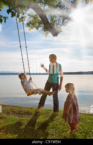 Mother playing with children on swing - Stock Photo