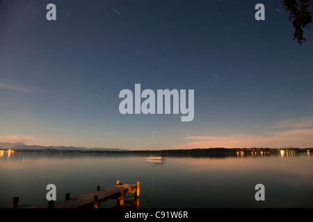 Wooden dock stretching into still lake - Stock Photo