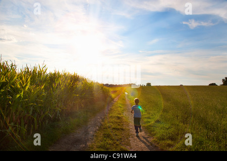 Boy playing on rural dirt path - Stock Photo
