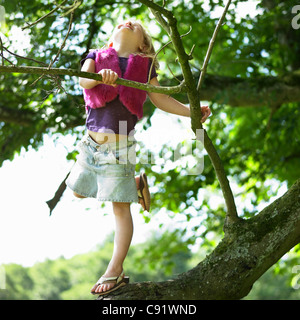Smiling girl climbing tree - Stock Photo