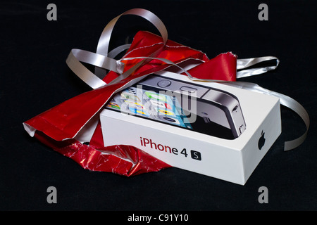 The iPhone 4S in its case, just opened from being gift-wrapped. - Stock Photo