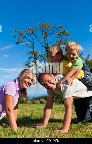 Happy family with two little boys playing in the grass on a summer meadow - Stock Photo