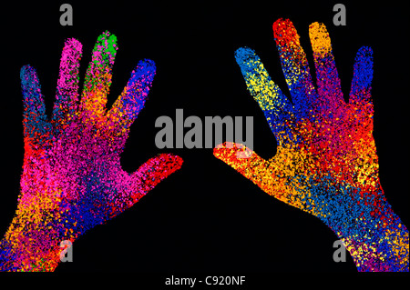 Childs multicoloured hand print on black background - Stock Photo