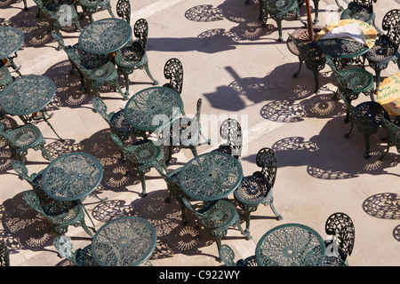 Painted wrought iron tables and chairs casting shadows in the bright afternoon sun beneath the Upper Barracca Gardens - Stock Photo