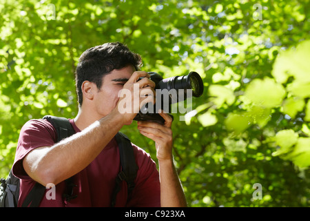 young hispanic man trekking among trees and taking pictures with dslr camera. Horizontal shape, side view, copy - Stock Photo