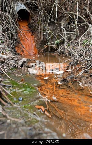 Rust colored water running through a drainage culvert, Alaska - Stock Photo