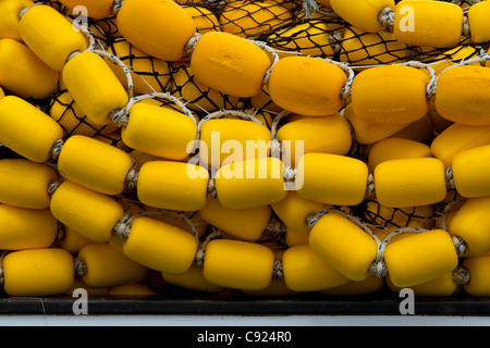Bright yellow corks and  commercial fishing seine net stacked on deck the of a vessel in Auke Bay, near Juneau, - Stock Photo