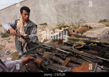 Former militia look at weapons at an army base, as part of a UN DDR program in Kabul, Afghanistan - Stock Photo