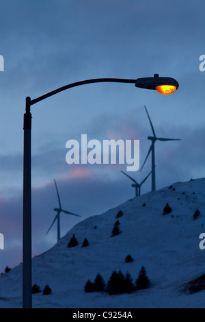 Lamp post glows warmly in late afternoon with wind turbines on top of Pillar Mountain behind City of Kodiak, Southwest - Stock Photo