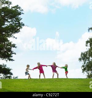 Girls playing tug-of-war in field - Stock Photo