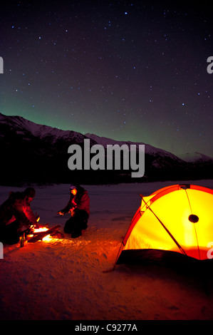 Two men camp on the frozen Eklutna Lake with the Northern Lights overhead, Chugach State Park, Southcentral Alaska, Winter