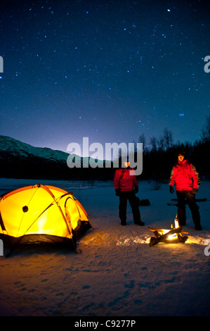 Two men warm themselves at a campfire while standing next to their lighted tent, Eklutna Lake in the Chugach State - Stock Photo
