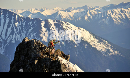 Couple stand on the summit of Bird Ridge in Chugach State Park with the scenic Chugach Mountains and in the background, - Stock Photo