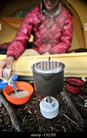 Woman prepares instant oatmeal with a backpacking stove at her tent, Crescent Lake, Chugach National Forest, Alaska - Stock Photo