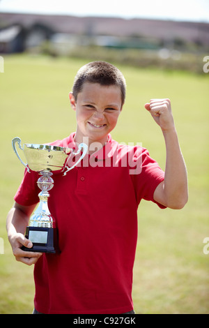 Boy cheering with trophy outdoors - Stock Photo