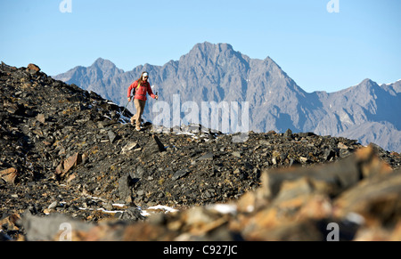 Woman hiking on the Crow Pass Trail along rocky ridge, Chugach Mountains, Southcentral Alaska, Autumn - Stock Photo