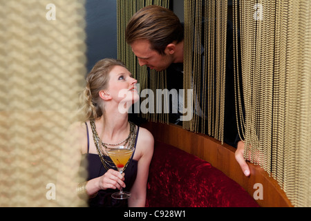 Couple talking through curtain in bar - Stock Photo