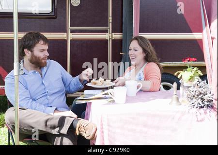 Couple picnicking outside trailer - Stock Photo