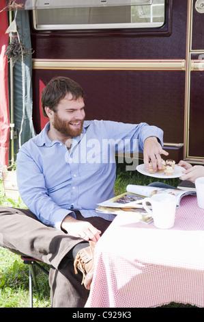 Man picnicking outside trailer - Stock Photo