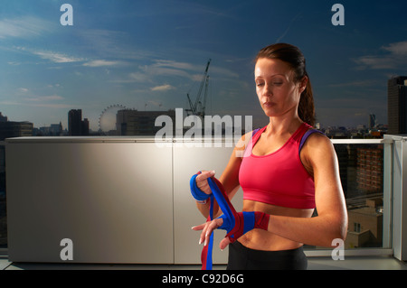 Boxer wrapping hands on urban rooftop - Stock Photo