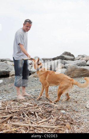 Man playing with dog on rocky beach - Stock Photo