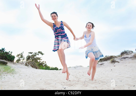 Woman and girl running on beach - Stock Photo