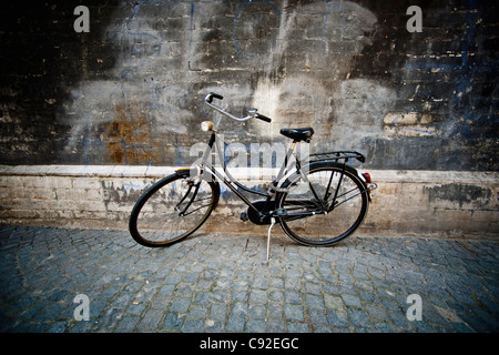 Vintage bicycle parked on cobbled street - Stock Photo